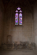 Abbey Church stained glass windows at Fontfroide Abbey near Narbonne, France. Fontfroide Abbey is a former Cistercian monastery in France, situated 15 kilometers south-west of Narbonne. It was founded in 1093 by Aimery I, Viscount of Narbonne, but remained poor and obscure, and needed to be refounded by Ermengarde, Viscountess of Narbonne. The abbey fought together with Pope Innocent III against the heretical doctrine of the Cathars who lived in the region. It was dissolved in 1791 in the course of the French Revolution. The premises, which are of very great architectural interest, passed into private hands in 1908, when the artists Gustave and Madeleine Fayet dAndoque bought it to protect the fabric of the buildings from an American collector of sculpture. They restored it over a number of years and used it as a centre for artistic projects. It still remains in private hands. Today it is open to paying guests.