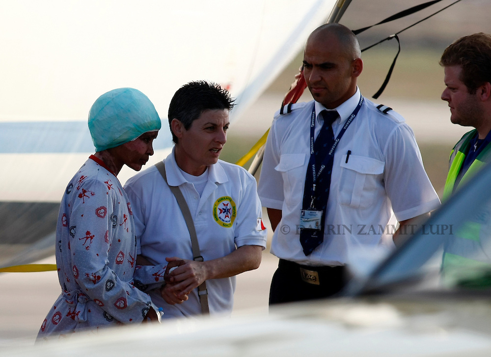 Shwejga Mullah (L) of Ethiopia is helped to a waiting ambulance after arriving at Malta International Airport,outside Valletta September 15, 2011. An Ethiopian nanny in the Gaddafi household who suffered horrific burns after she did not stop one of Muammar Gaddafi's grandchildren crying, has arrived in Malta for specialised medical treatment. Shwejga Mullah was recently discovered weak and alone in the home abandoned by Muammar Gaddafi's son Hannibal. She said that  Hannibal Gaddafi's wife Aline threw boiling water over her when she did not stop Hannibal Gaddafi's daughter crying and refused to beat the child. The nanny was brought over in a private plane chartered by the Maltese government.    REUTERS/Darrin Zammit Lupi (MALTA)