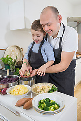 Father and son preparing dumplings in kitchen