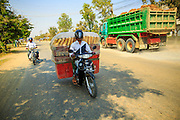 30 JANUARY 2013 - PHNOM PENH, CAMBODIA:  A bakery worker delivers bread on the a motorcycle near Phnom Penh, Cambodia. Cambodians and Vietnamese consume a lot of French style baguettes, a remnant of their time as a French colony.     PHOTO BY JACK KURTZ