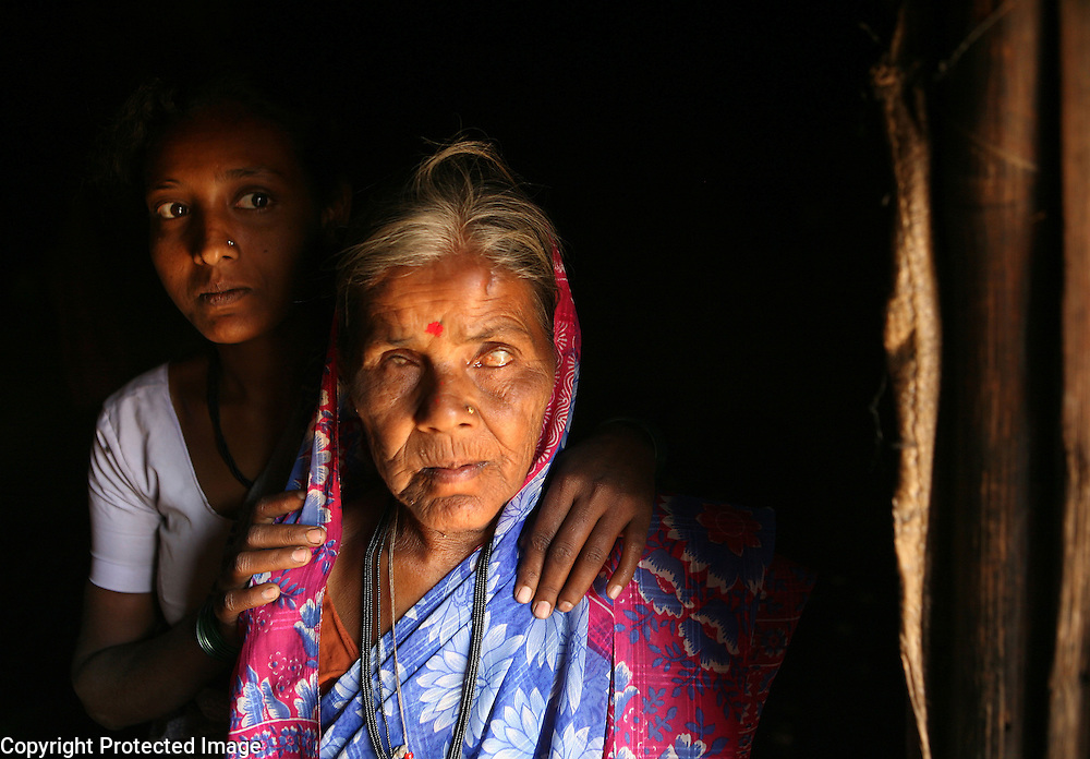 """Lalita Kamble, 50,  is photographed in the doorway of her home with her niece.  Kamble went blind at a young age and so, when she was eight years old, her parents dedicated her as a Devadasi.  """"They said you can be buried as a married person now because you're married to Yellamma,"""" she says, referring to the ritual of burying unmarried women in a lying down position while married women are buried sitting up. """"I wished I could get married but I knew no man would marry because because of my blindness,"""" she adds. Through a dairy program set up  by an organization called Vimochana Sangha which was founded to dismantle the Devadasi system, Kamble now takes care of a water buffalo and makes some income from the sale of its milk. Despite her acceptance of her lot in life, she does not support the continuation of the Devadasi system."""