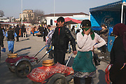 A young woman sells traditional Obi Nan bread from a wheelbarrow at the Chorsu Bazaar on 1st March 2014 in Taskhent in Uzbekistan. Obi nan is a kind of flatbread sold throughout Uzbekistan.