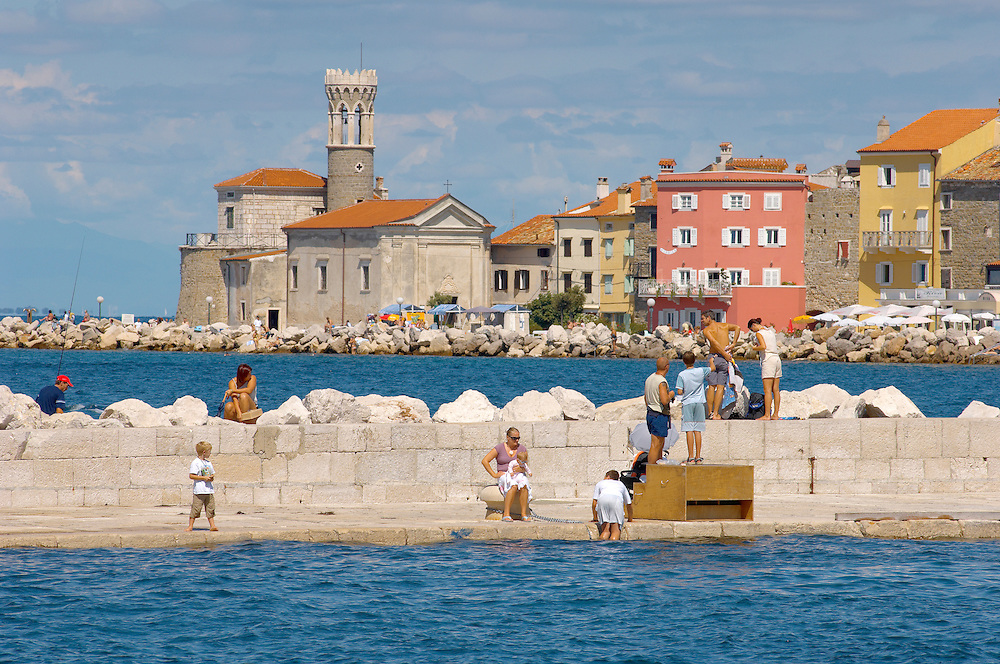 Harour entance with people relaxing and swimming off the harbour wall. Piran , Slovenia Visit our PHOTO COLLECTIONS OF SLOVANIAN  HISTOIC PLACES for more photos to download or buy as wall art prints https://funkystock.photoshelter.com/gallery-collection/Pictures-Images-of-Slovenia-Photos-of-Slovenian-Historic-Landmark-Sites/C0000_BlKhcYWnT4Sites/C0000qxA2zGFjd_k