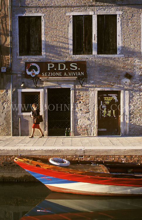 A woman walking by a colorful Gondola in Venice, Italy.