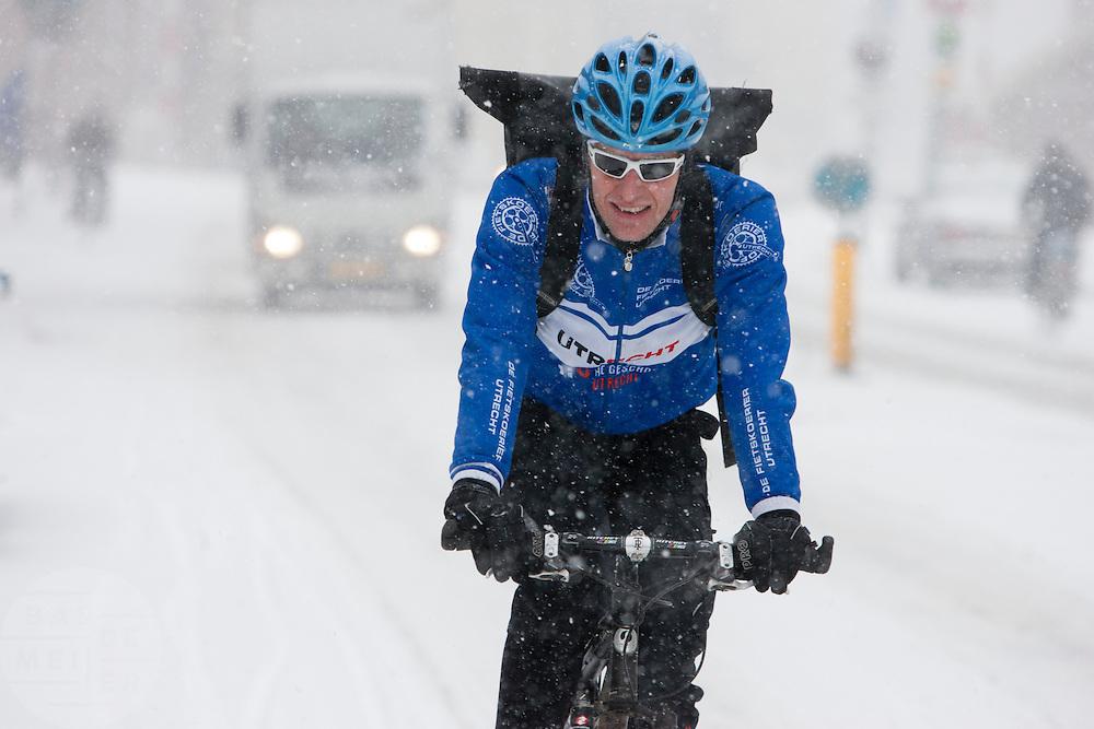 Een fietskoerier rijdt door de sneeuw.<br /> <br /> A bike messenger is riding in the snow