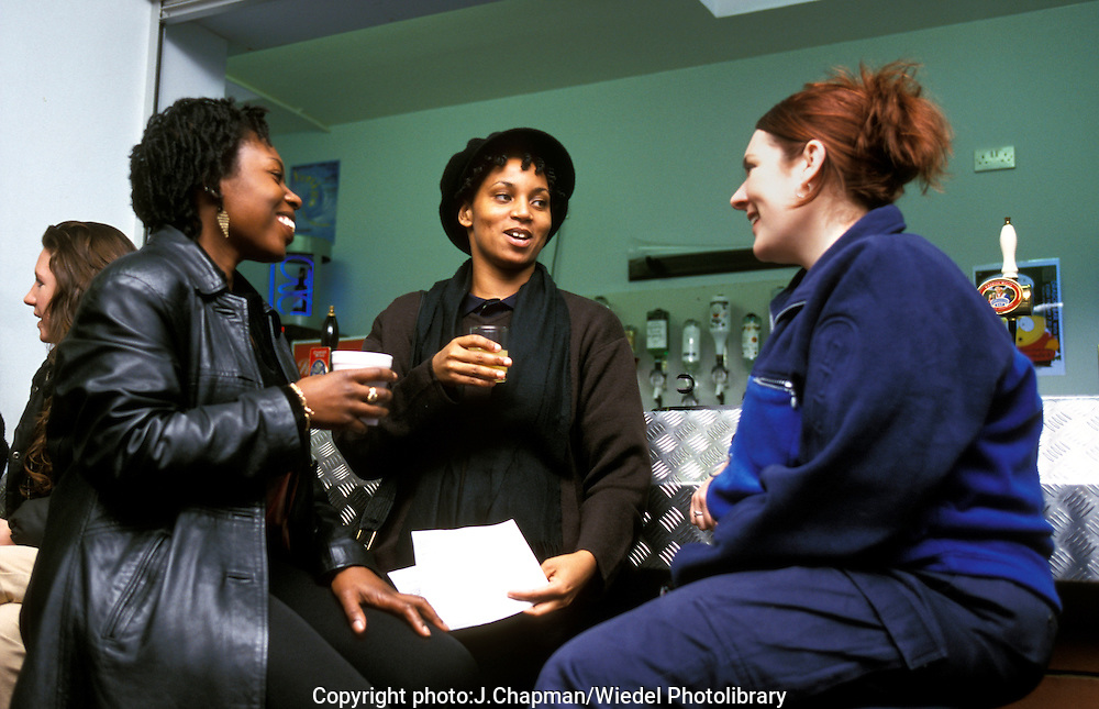 Three women  chatting over a drink in the student union bar.