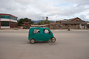 Street scene in Zhongdian, also known as Shangrila, in Yunnan, China. A three wheeled car in the dusty streets.