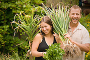 Sarah and Conner of Diggin' Roots CSA in Portland, Oregon joke around while harvesting garlic and parsley for their weekly baskets.
