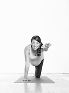 Pregnant woman (3rd trimester) streches and practices yoga on a mat.