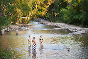 Bathers and dogs go for a dip in Boulder Creek at Eben G. Fine Park on a hot summer day in Boulder, Colorado.