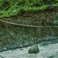 A trekker crosses a bridge over the monsoon-swollen Marsyandi River in the Marsyandi River Valley, east of Annapurna in Nepal.