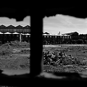 The closed Turner and Newall asbestos plant in Rochdale, England seen through a fence. This was the largest asbestos product manufacturing plant in the world which is only a few miles from Manchester. This plant was owned and operated by the now defunct company Turner and Newall (T & N). The history of this plant and Turner and Newall are forever tied to the deaths of numerous workers by disease from exposure to asbestos. The other important fact to note is that this plant used chrysotile asbestos from the mines in Quebec, Canada.