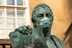 Statue of David Hume philosopher wearing facemask  on Royal Mile in Edinburgh, Scotland, UK