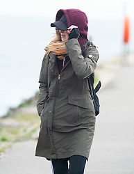 © Licensed to London News Pictures. 08/03/2019. Folkestone, UK. A lady holds on to her hood on a cloudy and windy afternoon at Folkestone seafront today with the weekend weather forecasters predicting 70mph winds with heavy rain.Photo credit: Grant Falvey/LNP