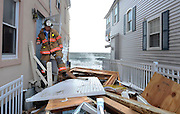 Milford Fire Department Capt. Christopher Waiksnoris checks for residents during another evacuation due to high tide in Milford, Conn. Hurricane Sandy made landfall Monday and caused multiple fatalities, halted mass transit and cut power to more than 6 million homes and businesses. (AP Photo/Jessica Hill)