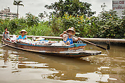 """17 NOVEMBER 2012 - BANGKOK, THAILAND:  Women paddle their canoe to a nearby market in the Thonburi section of Bangkok. Bangkok used to be known as the """"Venice of the East"""" because of the number of waterways the criss crossed the city. Now most of the waterways have been filled in but boats and ships still play an important role in daily life in Bangkok. Thousands of people commute to work daily on the Chao Phraya Express Boats and fast boats that ply Khlong Saen Saeb or use boats to get around on the canals on the Thonburi side of the river. Boats are used to haul commodities through the city to deep water ports for export.    PHOTO BY JACK KURTZ"""