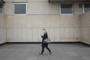 A woman walks along Bankside looking at her mobile phone on 19th February 2017 in London, United Kingdom. From the series Our Small World, an observation of our mobile phone obsessions