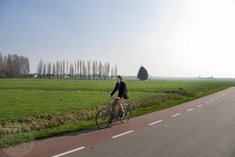 Een jongeman fietst door de polder bij Berkel en Rodenrijs.<br /> <br /> A young man is cycling in the polder near Berkel en Rodenrijs.