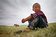 A young horse rider waits before the start of the Nadaam (Nadam) festival, a horse race taking place every year in Ulan Bator in summer. Young Mongolians usually learn to ride horses before they can even walk...