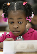 Mechanicstown Elementary School third-grader Jene Ennis uses a magnifying glass to look at details of an enlarged copy of a dollar bill during a presentation on money and banking by Debra Weaver and Kezia LaBuda of Orange County Trust at the school in Middletown on Jan. 16, 2008.