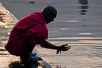 """India, Nasik, 2006. Newly shaven, a pilgrim cleans himself before """"puja"""" in the Ramkund, which holds water from the Godavari River."""