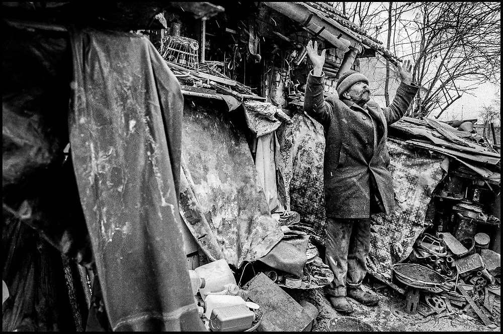 """58 year old Catholic Croat. Praying outside his bombed out home, Ostrovo, Croatia. He's describes his place """"as not fit for a dog to live in"""" 1998"""