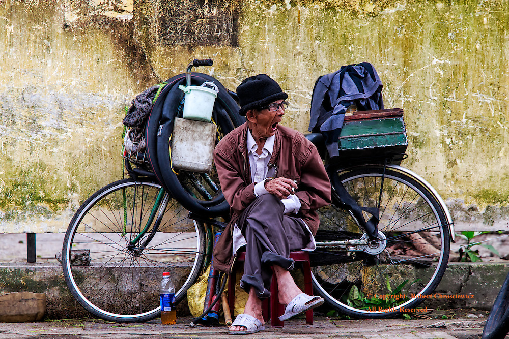 Yawning For Business: An elderly man, sitting by his mobile bicycle work shop, yawns deeply awaiting his next customer, Hue Vietnam.