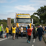 13 local activists locked themselves in specially made arm tubes to block the entrance to Quadrilla's drill site in New Preston Road, July 03 2017, Lancashire, United Kingdom. Protesters try to stop a truck owned by Pete Marquis, a pro-fracker and highly controversial local entrepeneur who owns a hauling company. The 13 activists included 3 councillors; Julie Brickles, Miranda Cox and Gina Dowding and Nick Danby, Martin Porter, Jeanette Porter,  Michelle Martin, Louise Robinson,<br /> Alana McCullough, Nick Sheldrick, Cath Robinson, Barbara Cookson, Dan Huxley-Blyth. The blockade is a repsonse to the emmidiate drilling for shale gas, fracking, by the fracking company Quadrilla. Lancashire voted against permitting fracking but was over ruled by the conservative central Government. All the activists have been active in the struggle against fracking for years but this is their first direct action of peacefull protesting. Fracking is a highly contested way of extracting gas, it is risky to extract and damaging to the environment and is banned in parts of Europe . Lancashire has in the past experienced earth quakes blamed on fracking.