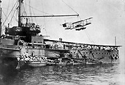 British Royal Navy warship with launching platform for the biplane which is suspended above it, c1914.