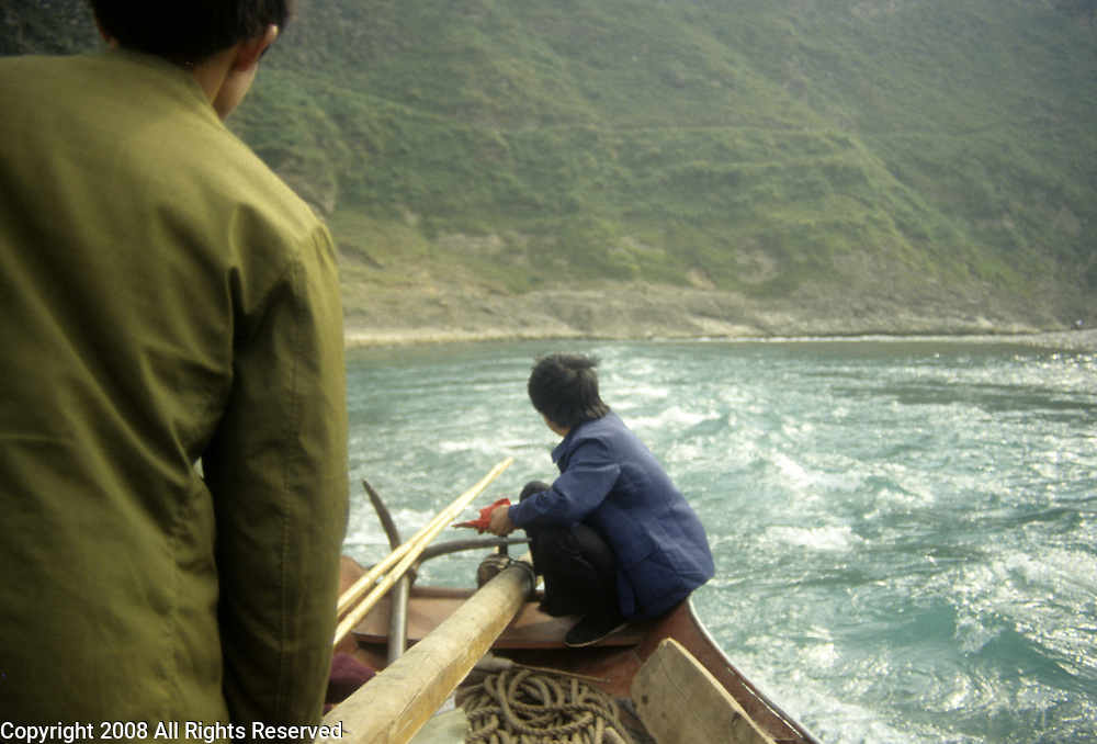 Chinese navigators steer a small boat during the a Chinese River cruise in October 1992.