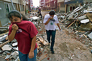 1/27/ 99 AL DIAZ/HERALD STAFF--Walking through their neighborhood, Edilce Hoyos and sister Diana Hoyos cover their faces as they walk pass a domolished building in Armenia struck hard by Monday's earthquake in Colombia.