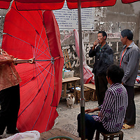 A vendor struggles to set up her umbrella as the skies threaten rain at the morning farmer's market in the center of Heshun.