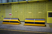 Huge yellow and black security street barrier blocking the entrance to a modern building in Southwark, London, UK. These barriers are known as road blockers or rising kerbs and are designed to keep vehicles out an also to prevent vehicles leaving.