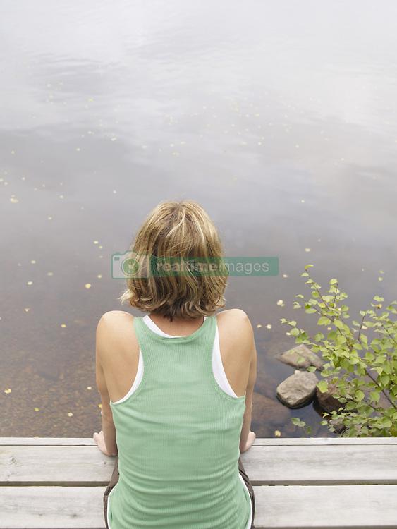 Aug. 23, 2007 - Woman sitting on dock.. Model & Property Released (MR&PR) (Credit Image: © Cultura/ZUMAPRESS.com)