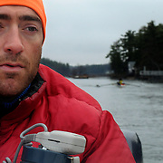 """4/27/11 -- BRUNSWICK, Maine. Eliot Pitney, Coach of Bowdoin Women's Crew, drills his team on the new Meadows river in late April. Pitney has coached at Bowdoin for the last 4 years. and before that at Bates.  """"This time of year,"""" he says, """" I'm ready to quit -- I'm just exhausted. But, give me a week off and then I'm right back at it -- ready to go for fall!""""  Pitney, also working on a  Master's in Mechanical Engineering puts in about 12 hours a week on the water - not including trips to and from races. """"It gets in your blood,"""" he says of rowing. """"You love it or hate it. . .""""   Photo by Roger S. Duncan."""