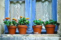 Flower pots sit on window ledge with lace curtains in Provence village, France