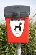 Close up of red litter bin for dog waste only, Suffolk, England