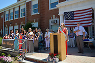 Wantagh, New York, USA. July 4, 2016.  KAYLA KNIGHT, Miss Wantagh 2014, sings God Bless America, with Hon. CHRISTOPHER QUINN standing to right of her and wearing red white and blue tie, at the start of the at the 60th Annual Miss Wantagh Pageant, an Independence Day tradition on Long Island. Judge Christopher Quinn is the Nassau County Supervising Judge of the County Court, and Acting Supreme Court Justice. Since 1956, the Miss Wantagh Pageant, which is not a beauty pageant, crowns an area high school student based mainly on academic excellence and community service.