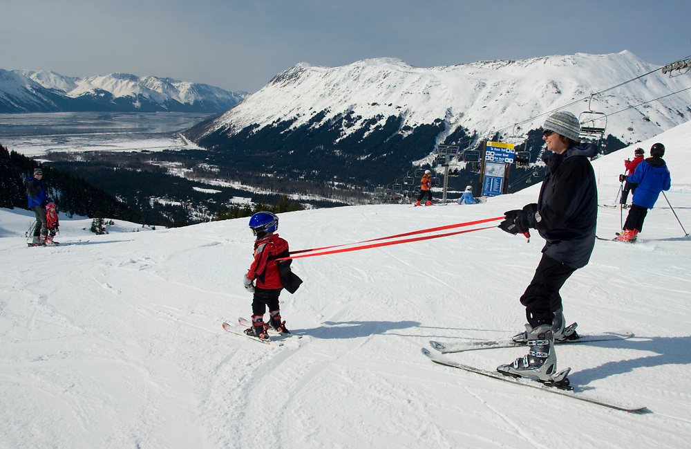 Using a tether, a father teaches his young child to ski.