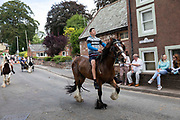 A young boy rides a brown horse bareback down the towns road at Appleby Horse Fair, the biggest gathering of Gypsies and travellers in Europe, on 14th August, 2021 in Appleby, United Kingdom. Appleby Horse Fair attracts thousands from Gypsy, Romany, and traveller communities annually, making it the biggest gathering of its kind in Europe. Generally held for a week every June, the fair was postponed in 2020 and pushed forward to August in 2021 due to Coronavirus.
