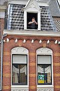 Nederland, Nijmegen, 3-6-2015Een monumentaal huis in de oude binnenstad staat te koop. Een man in het raam op de zolder kijkt op zijn mobiel, mobieltje, gsm, smartphone,telefoon