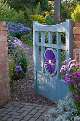 Wooden gate with aster motif leading into the garden at Old Court Nurseries, Colwall