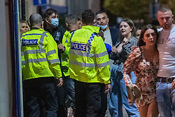 © Licensed to London News Pictures. 25/09/2020. Oxford, UK. Thames Valley Police officers attempt to disperse people on Cowley Road, Oxford after bars closed at 10pm as new restrictions brought in to curb increasing cases of the COVID-19 coronavirus take effect. Photo credit: Peter Manning/LNP