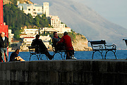 Locals sitting on benches on the Porporela (breakwater) in late afternoon sunlight, Dubrovnik old town, Croatia