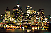 New York City skyline at night with Brooklyn Bridge in the foreground