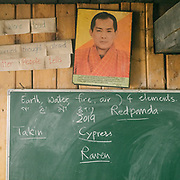 Blackboard and a portrait of the 5th King. Visiting the only school in Laya village.