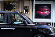 Picture of glistening lips with red dripping lipstick on Bond Street on 28th January 2021 in London, United Kingdom. Bond Street is one of the principal streets in the West End shopping district and is very upmarket. It has been a fashionable shopping street since the 18th century. The rich and wealthy shop here mostly for high end fashion and jewellery.