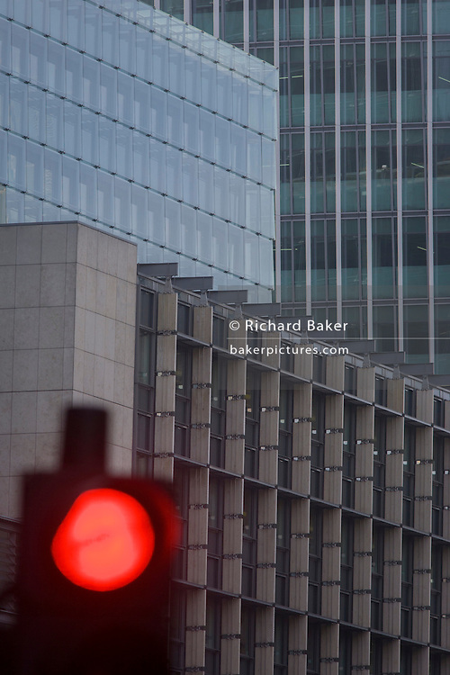 Mixed architecture of generic City of London office buildings and red Stop traffic light in the heart of the capital's financial district.