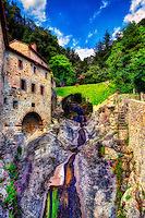 """""""Water flow passage to the Convent of cells founded by Saint Francis – Cortona""""…<br /> <br /> St. Francis came to Cortona to preach in 1211, and here at the foot of Mount Sant'Egidio found the solitude he was looking for. A young nobleman who went on to become the Blessed Guido, one of his first followers, offered him the place as a prayer retreat. From that moment St. Francis and his followers stayed in this isolated spot on the way to and from Assisi and other places where they were preaching. There was no hermitage in St. Francis's time, however, and the saint slept on the bare rock. After he died in 1226, the first stone """"cells"""" were built and a small oratory. What we see today is the result of the XVI century construction work. Le Celle stood abandoned until 1537 when it was granted by the Bishop of Cortona to the recently founded Third Order of Franciscans, known as the Capuchins. The hermitage was considerably enlarged by the Capuchins, who in 1634 erected a new chapel to take the place of a more ancient one. This new chapel was consecrated to St Anthony of Padua and reflects the Capuchins simple, unpretentious architectural and decorative style. I found Le Celle to be one of the pleasant surprises in and around Cortona. The tiny cells built into the side of the mountain with a stream descending along the structural edge creates a surreal and picturesque vision of Saint Francis' image of God and nature. Imagine the spiritual solitude as Saint Francis would take hermitage here for days of ecstatic meditation with only a loaf of bread, listening to his beloved waterfall beneath a small window."""