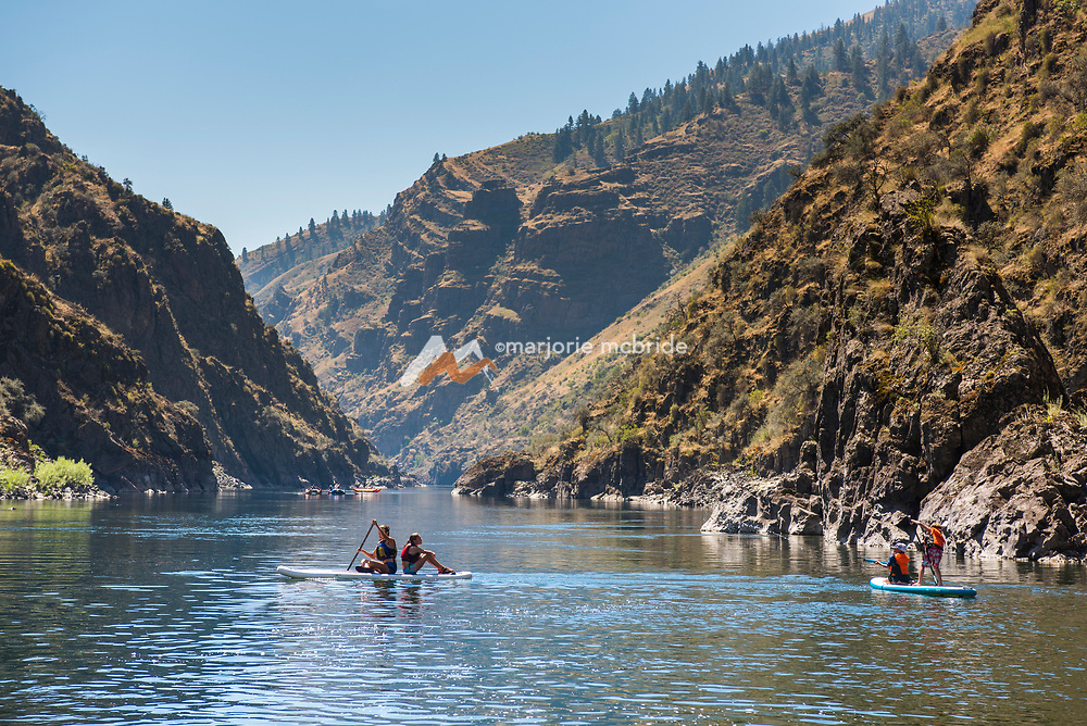 Kids having fun on the water while paddle boarding during a rafting trip on the Main Lower Salmon River, Hammer Creek to Hellar Bar, Idaho.